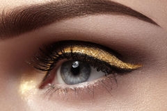 Beautiful macro shot of female eye with ceremonial makeup. Perfect shape of eyebrows, eyeliner and pretty gold line on eyelid. Cosmetics and make-up. Closeup stock images