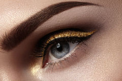 Beautiful macro shot of female eye with ceremonial makeup. Perfect shape of eyebrows, eyeliner and pretty gold line on eyelid. Cosmetics and make-up. Closeup stock photos