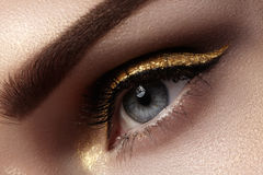 Beautiful macro shot of female eye with ceremonial makeup. Perfect shape of eyebrows, eyeliner and pretty gold line on eyelid Stock Image