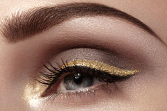 Beautiful macro shot of female eye with ceremonial makeup. Perfect shape of eyebrows, eyeliner and pretty gold line on eyelid. Cosmetics and make-up. Closeup Royalty Free Stock Photo