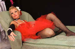 Beautiful madam on sofa. Beautiful blonde woman dressed up as old fashioned madam or prostitute, could also be a sexy elf or mrs. claus for christmas, looking Royalty Free Stock Photography