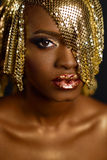 Beautiful Magic Woman Portrait. Golden Makeup. Model Afro-american Girl face with gold skin, lips, make-up and accessories.  royalty free stock image