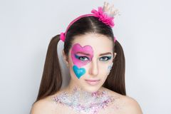Hearts make up. Beautiful magical charming woman, love princess with big and small painted hearts on face. hair tails. Figure paint her cheek blush, bright royalty free stock photos