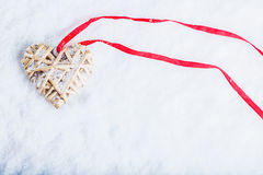 Beautiful magical vintage beige heart tied with a red ribbon on a white snow background. Winter and Christmas concept Royalty Free Stock Image