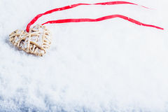 Beautiful magical vintage beige heart tied with a red ribbon on a white snow background. Winter and Christmas concept Royalty Free Stock Photos
