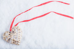 Beautiful magical vintage beige heart tied with a red ribbon on a white snow background. Winter and Christmas concept Royalty Free Stock Photography