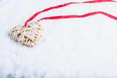 Beautiful magical vintage beige heart tied with a red ribbon on a white snow background Royalty Free Stock Photos