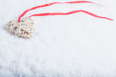 Beautiful magical vintage beige heart tied with a red ribbon on a white snow background. Winter and Christmas concept Royalty Free Stock Images