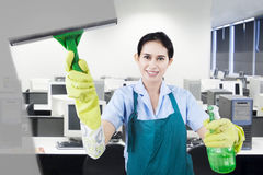 Beautiful maid cleans the dirty mirror Stock Photo