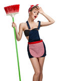 Beautiful maid standing tired after spring cleaning with broom Royalty Free Stock Image