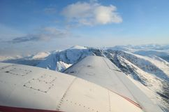 Beautiful and majestic snowy mountain landscape with ocean in the background with aircraft wings Stock Images