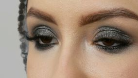 Beautiful make-up smoky eyes of a professional girl model. Women`s brown eyes with long eyelashes close up view. Beautiful make-up smoky eyes of a professional stock video
