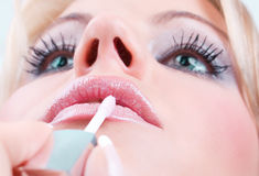 Beautiful makeup applies a slick of pink lip Stock Image
