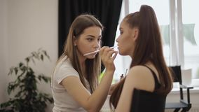 Beautiful makeup artist applies lipstick. Hand of make-up master, painting lips of young beauty redhead model. Make up stock video footage