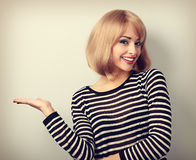 Beautiful makeup blond woman holding and presenting something in Royalty Free Stock Photo