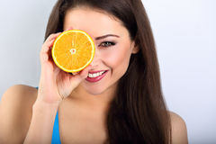 Beautiful makeup brunette woman holding fresh orange fruit near Royalty Free Stock Photo