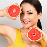 Beautiful makeup brunette woman holding fresh red grapefruit near the face and looking happy on empty space blue background. royalty free stock photography
