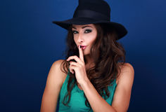 Beautiful makeup female model in hat showing secret sign on blue Stock Images