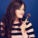 Beautiful makeup happy woman holding make-up powder brush on blu Stock Images