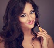 Beautiful makeup happy woman holding make-up powder brush. Curly Stock Photography