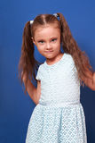 Beautiful makeup kid girl with long hair posing in fashion dress Royalty Free Stock Images