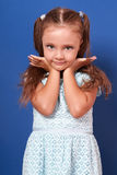 Beautiful makeup kid girl posing in dress with hands under face Royalty Free Stock Image