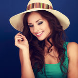 Beautiful makeup smiling woman in summer hat with curly long bro. Wn hair looking down on blue background. Toned closeup portrait Stock Photography