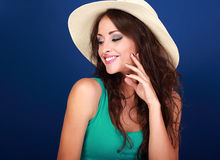 Beautiful makeup smiling woman in summer hat with curly long bro. Wn hair with manicured nails on blue background Stock Photography