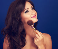 Beautiful makeup woman applying make-up powder by the brush on c Stock Photography