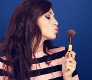 Beautiful makeup woman blowing on make-up powder brush on blue b Stock Photo