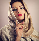 Beautiful makeup woman with red lipstick and long lashes posing. With head covered orient traditional shawl in studio Stock Photos