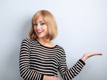 Beautiful makeup young blond woman holding and presenting someth Royalty Free Stock Photos