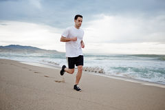 Beautiful male athlete runs along the beach along the sea, mountain beach background. Morning jog, fitnes and healthily lifestyle, sport and health concept stock photo