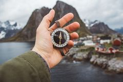 Beautiful male hand holds a magnetic compass against the background of the houses and mountains rocks over fjord royalty free stock images