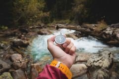 A beautiful male hand with a yellow watch strap holds a magnetic compass in a coniferous autumn forest against a. Mountain river with rocky stones. The concept royalty free stock images