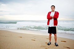 Beautiful male runner with crossed hands rest standing on the sand on the waves background. Morning jogging, fitnes and healthily lifestyle, sport and healthy royalty free stock images