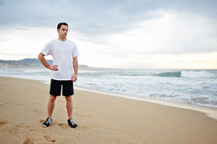 Beautiful male runner dressed in the white t-shirt resting after intensive morning jogging standing on the beach. Morning jog, fitnes and healthily lifestyle royalty free stock photography