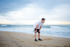 Beautiful male sportsman dressed in the white t-shirt standing on the sand resting after intensive morning jog. Morning jog, fitnes and healthily lifestyle stock images