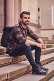 Beautiful male with stylish haircut and beard, wearing a fleece shirt and jeans, sitting on steps against an old stock image