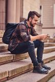 Beautiful male with stylish haircut and beard, wearing a fleece shirt and jeans, sitting on steps against an old. A smiling beautiful student with stylish Royalty Free Stock Photography