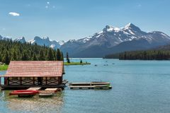 Scenic view of Maligne Lake, Jasper National Park, Alberta, Canada. Beautiful Maligne Lake with a boathouse and canoes and snow covered mountains, Jasper Stock Image