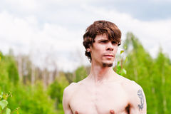 Beautiful man. Portrait of a man with a tattoo on the background of nature Stock Photos