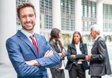 Beautiful man on the background of business people Royalty Free Stock Image