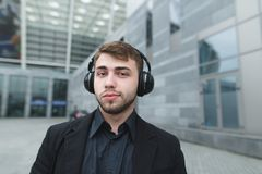 Beautiful man with a beard and a suit who listens to music in headphones against a background of urban landscape. Stock Images