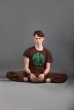 Beautiful man doing yoga  baddha konasana. On a gray background Stock Image