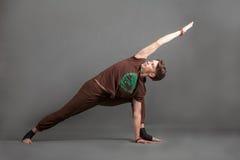 Beautiful man doing yoga utthita parshvakonasana. Beautiful man doing yoga on a white background Stock Photos