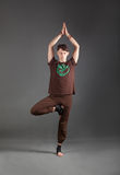Beautiful man doing yoga vrikshasana. Beautiful man doing yoga on a gray background Stock Photography