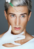 Beautiful man face and beautician hands with syringe Royalty Free Stock Photography
