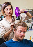 Beautiful man at the hairdresser blow drying his hair Royalty Free Stock Photo