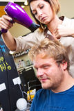 Beautiful man at the hairdresser blow drying his hair Stock Photo